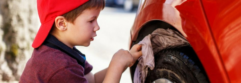A child cleaning a car's tire