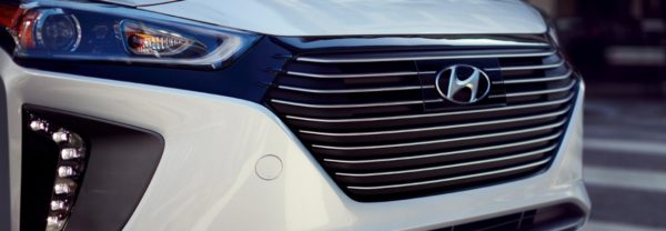 A close-up of a new Hyundai car's front grille and logo
