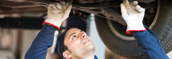 Service technician inspects a car's undercarriage