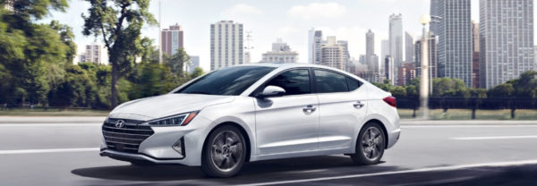 White 2019 Hyundai Elantra driving on a highway away from a city.